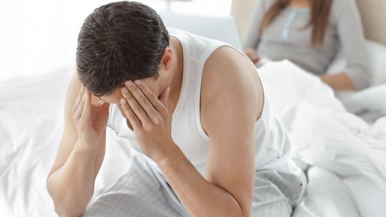 Uomo con problemi di eiaculazione precoce seduto sul letto