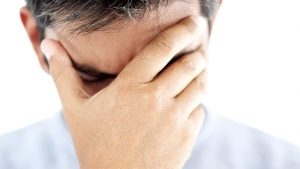 Uomo imbarazzato da un problema di disfunzione erettile si copre il viso con una mano