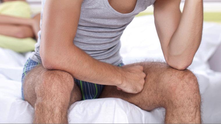 Uomo seduto su un letto pensa ai problemi di impotenza